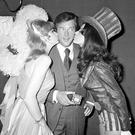 File photo dated 04/01/71 of Roger Moore being kissed from Miss UK and Miss USA. Sir Roger has died in Switzerland after a short battle with cancer, his family has announced. PRESS ASSOCIATION Photo. Issue date: Tuesday May 23, 2017. See PA story DEATH Moore. Photo credit should read: PA Wire