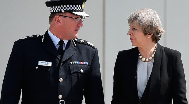 Britain's Prime Minister Theresa May walks with Chief Constable of Greater Manchester Police, Ian Hopkins. / AFP PHOTO / Oli SCARFFOLI SCARFF/AFP/Getty Images
