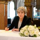 Prime Minister Theresa May writes a message at Manchester Town Hall in Manchester after the terror attack. Pic: Ben Birchall/PA Wire