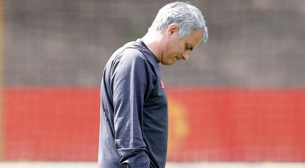 United in grief: Jose Mourinho in sombre mood yesterday as his Manchester United team observed a silent tribute to bomb victims
