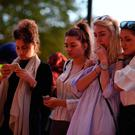 People pause in front of candles set up in front of floral tributes in Albert Square in Manchester, northwest England on May 23, 2017, in solidarity with those killed and injured in the May 22 terror attack at the Ariana Grande concert at the Manchester Arena.