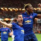 Manchester United's Henrikh Mkhitaryan, left, celebrates scoring with teammate Paul Pogba during the Europa League soccer final match between Ajax and Manchester United at the Friends Arena in Stockholm, Sweden, Wednesday May 24, 2017. (Anders Wiklund/TT via AP)