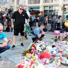 Former boxer Ricky Hatton (black t-shirt) looks at tributes in St Ann's Square, Manchester, before a minute's silence to remember the victims of the terror attack in the city earlier this week.