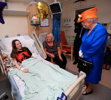 MANCHESTER, ENGLAND - MAY 25:Queen Elizabeth II speaks to Millie Robson, 15, from Co Durham, and her mother, Marie, during a visit to the Royal Manchester Children's Hospital to meet victims of the terror attack on May 25, 2017 in Manchester, England. Queen Elizabeth visited the hospital to meet victims of the Manchester Arena terror attack and to thank members of staff who treated them. (Photo by Peter Byrne/WPA Pool/Getty Images)