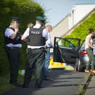 Police officers at the scene of a double murder in the Upper Ramone Park area. (Photo - Kevin Scott / Belfast Telegraph)