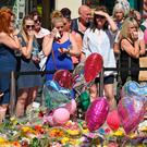 Senseless savagery: Members of the public look at tributes left for the people who died in Monday's terror attack in Manchester