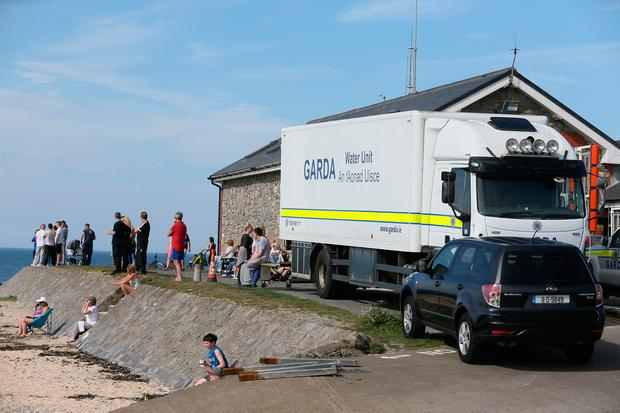 People watch as a Garda water unit undertake a search in Skerries harbour. PA