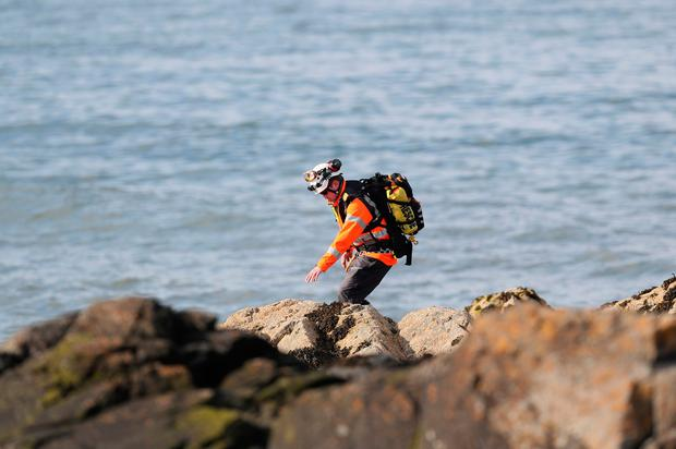 A member of the Irish coast guard searches the coastline in Skerries as a search and rescue operation is under way for a missing fisherman after a boat sank in the Irish Sea. PA