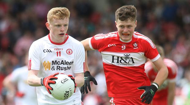 Close attention: Tyrone's Peter Og McCartan is pursued by Dara Rafferty. Photo: Lorcan Doherty/Presseye