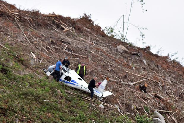 The scene at the mountain top near Castlewellan where a light plane crashed on Monday afternoon. Avaition club members move the remains of the plane down the mountain. Photo by Tony Hendron/Presseye