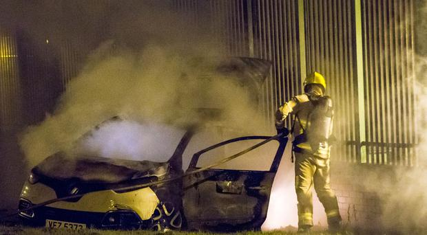 Police and Fire Fighters tend to a stolen car that was set alight in the Ross Road area of Divis in Belfast on May 30th 2017 (Photo - Kevin Scott / Belfast Telegraph)