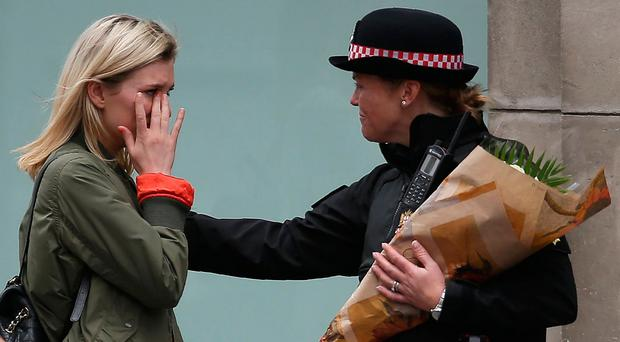 A woman reacts after asking a Police officer to lay flowers near London Bridge in London on June 4, 2017, as a tribute to the victims of the June 3 terror attack. [Photo: Olivia Leal/AFP/Getty Images
