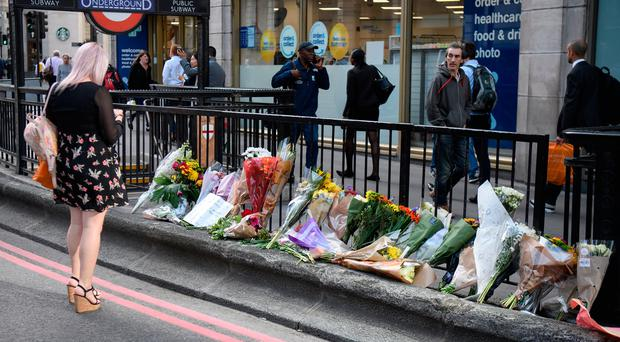 A commuter looks at some of the floral tributes on London Bridge after it was reopened following the June 3rd terror attack on June 5, 2017 in London, England. Seven people were killed and at least 48 injured in terror attacks on London Bridge and Borough Market. Three attackers were shot dead by armed police. (Photo by Leon Neal/Getty Images)
