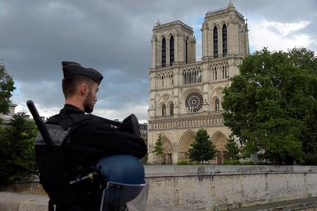 A French gendarme holds his helmet as he stands on a bridge near the entrance of Notre-Dame cathedral in Paris on June 6, 2017. AFP/Getty Images
