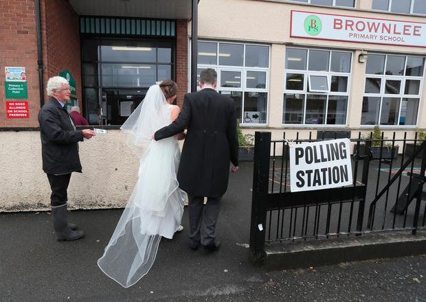 Alliance candidate for West Belfast Sorcha Eastwood arrives to cast her vote in the 2017 General Election, with her husband, Dale Shirlow, at a polling station in Lisburn, Northern Ireland, still wearing her wedding dress after they were married earlier in the day. Brian Lawless/PA Wire