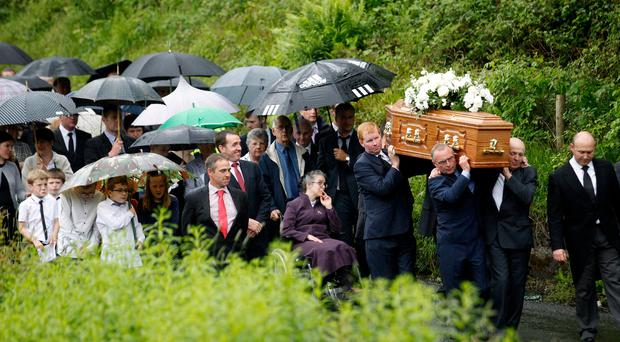 Mourners carry the coffin of Presbyterian minister Rev Roy Campbell