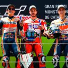 Italian Andrea Dovizioso (centre) celebrates on the podium next to Spainards Marc Marquez (left) second and Dani Pedrosa, third, after winning the MotoGp of Catalunya at Circuit de Catalunya