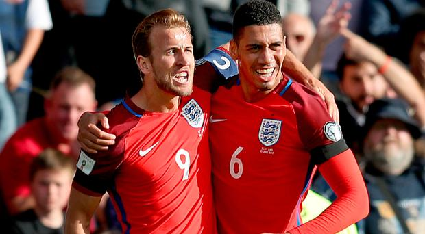 Late show: Harry Kane celebrates with Chris Smalling after scoring England's injury-time leveller