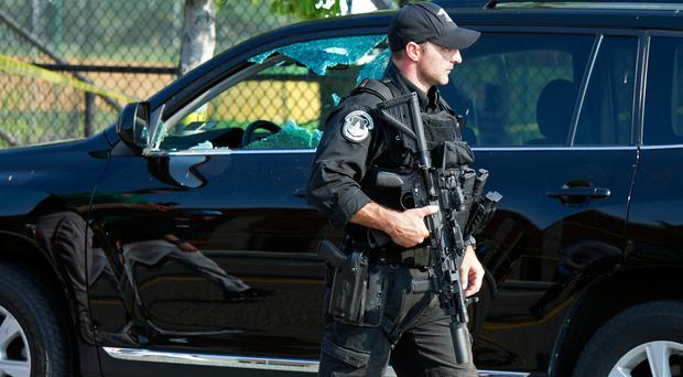 A Capitol Hill Police officer walks past an automobile with the driver's window damaged at the scene of a shooting in Alexandria, Va., Wednesday, June 14, 2017, where House Majority Whip Steve Scalise of La. was shot at a Congressional baseball practice. (AP Photo/Cliff Owen)