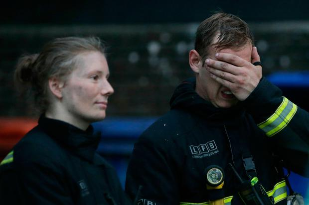 Firefighters react as a huge fire engulfs the Grenfell Tower early June 14, 2017 in west London. AFP/Getty Images