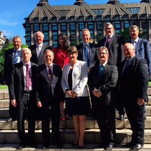 DUP leader Arlene Foster with the party's 10 MPs outside the Houses of Parliament in London.