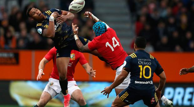 High and mighty: Tevita Li of the Highlanders catches the ball as Lions winger Jack Nowell challenges for it. Photo: David Rogers/Getty Images