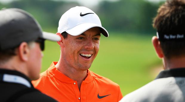 Rory McIlroy smiles while talking with Louis Oosthuizen of South Africa during a practice round prior to the 2017 US Open at Erin Hills.