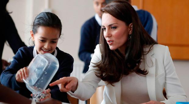 The Duchess of Cambridge chats with a child during her visit the 1851 Trust roadshow at Docklands Sailing and Watersports Centre in London
