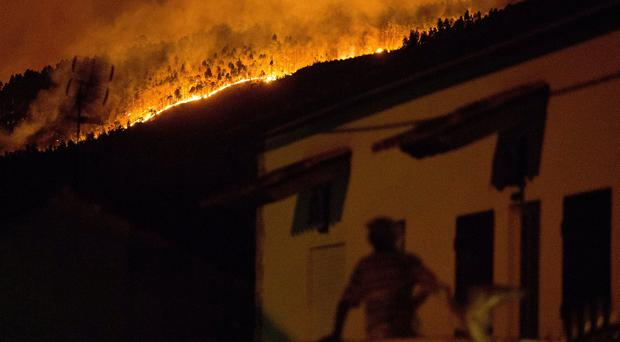 A man on the balcony of a house looks up at a forest fire raging on a hillside above the village of Avelar central Portugal before sunrise Sunday