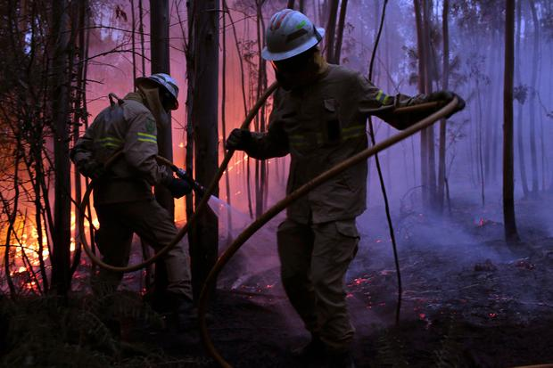 Portuguese National Republican Guard firefighters work to stop a forest fire from reaching the village of Avelar, central Portugal, at sunrise Sunday, June 18 2017. (AP Photo/Armando Franca),