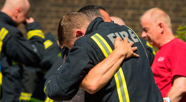 A fighfighter and a man embrace at the Latymer Community Centre, before observing a minute's silence near to Grenfell Tower in west London after a fire engulfed the 24-storey building on Wednesday morning. Dominic Lipinski/PA Wire