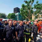 Police and firefighters halt work to join residents for a minute's silence in honour of the victims and those affected