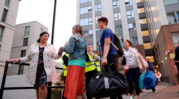 Residents leave a tower block on the Chalcots Estate in Camden, London, as the building is evacuated in the wake of the Grenfell Tower fire to allow