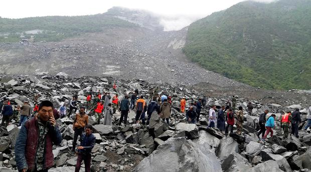 Emergency personnel and locals work at the site of a landslide in Xinmo village in Maoxian County in southwestern China's Sichuan Province, Saturday, June 24, 2017. Dozens of people are feared buried by a landslide that unleashed huge rocks and a mass of earth that crashed into their homes in southwestern China early Saturday, a county government said. (Chinatopix via AP)