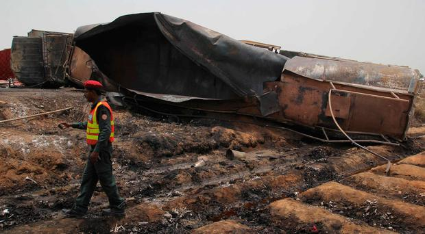 Pakistani rescue workers gather beside an oil tanker which caught fire following an accident on a highway near the town of Ahmedpur East
