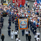 Crowds watch an Orange Order parade take place in Belfast