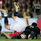 All Blacks loose forward Jerome Kaino, right, upends Lions halfback Conor Murray during the first test match. Photo: Brett Phibbs/New Zealand Herald via AP