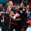 Strike it rich: Crues ace Jordan Owens is mobbed after finding the net at Seaview
