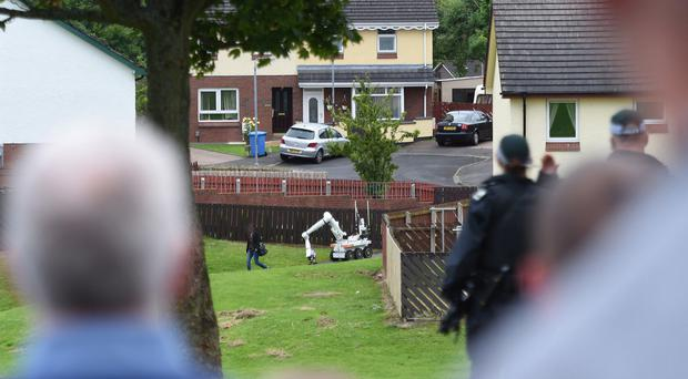 Concerned police call out a warning as a woman walks past the robot dealing with the suspect device in Galliagh