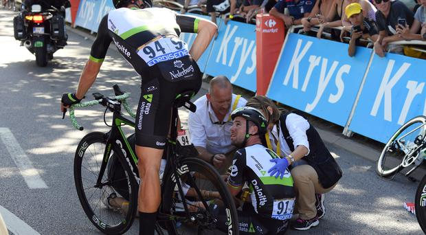 Bash: Britain's Mark Cavendish gets treatment after crashing