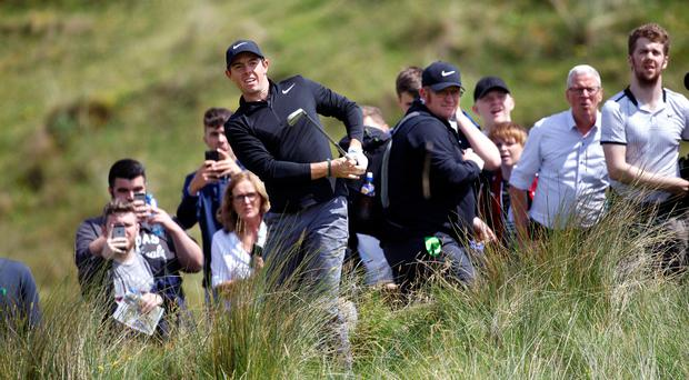Homing in: Rory McIlroy plays from the rough during yesterday's Pro-Am event at Portstewart