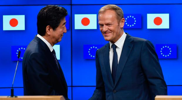 European Council President Donald Tusk (right) shakes hands with Japanese Prime Minister Shinzo Abe during a press conference after an EU-Japan summit in Brussels yesterday. Photo: Getty