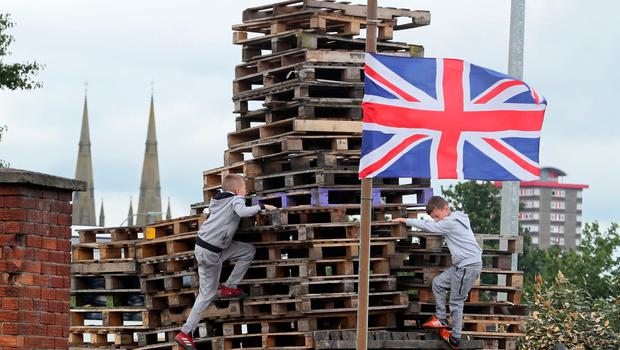 Children play on a bonfire in the village area of Belfast, Northern Ireland on July 10, 2017, ahead of the traditional 11th night bonfires  The Eleventh Night refers to the night before the Twelfth of July, an annual Protestant commemoration of the famous battle were Protestant King William III of Orange defeated Catholic King James II at the battle of the Boyne on July 12, 1690. / AFP PHOTO / Paul FAITHPAUL FAITH/AFP/Getty Images