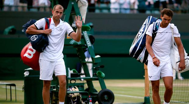 Rafael Nadal after losing to Gilles Muller (left) on day seven of the Wimbledon Championships at The All England Lawn Tennis and Croquet Club, Wimbledon. Steven Paston/PA Wire.