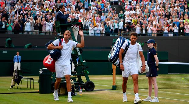 Marathon effort: Gilles Muller and Rafa Nadal leave following their epic battle on Court One