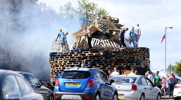 The scene on Love Lane in Carrickfergus as the local community rebuild a bonfire after the original bonfire they built was burnt on Monday evening. Picture by Matt Mackey / presseye.com
