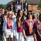 Bandsmen and members of the Orange Order march down the Crumlin Road, past Ardoyne shops, in North Belfast after a deal was struck last year between the Orange Order and the Ardoyne Residents Association.