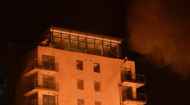Firefighters on the roof of the Victoria Place apartments, Wellwood Street, Belfast. Picture By: Arthur Allison.