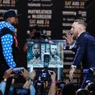 Conor McGregor, right, taunts Floyd Mayweather Jr. while pausing for photos during a news conference at Staples Center on Tuesday, July 11, 2017, in Los Angeles. The two will fight in a boxing match in Las Vegas on Aug. 26. (AP Photo/Jae C. Hong)