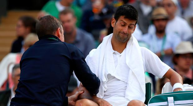 No good: Novak Djokovic receives medical attention but he was unable to complete his match against Tomas Berdych. Photo: Julian Finney/Getty Images)